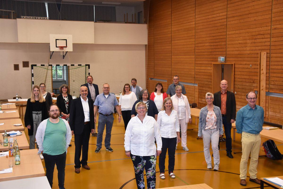 Die Mitglieder der Mitarbeitervertretung des Ordinariats Würzburg stehen bei einem Treffen mit dem geforderten Mindesabstand in einer Turnhalle.