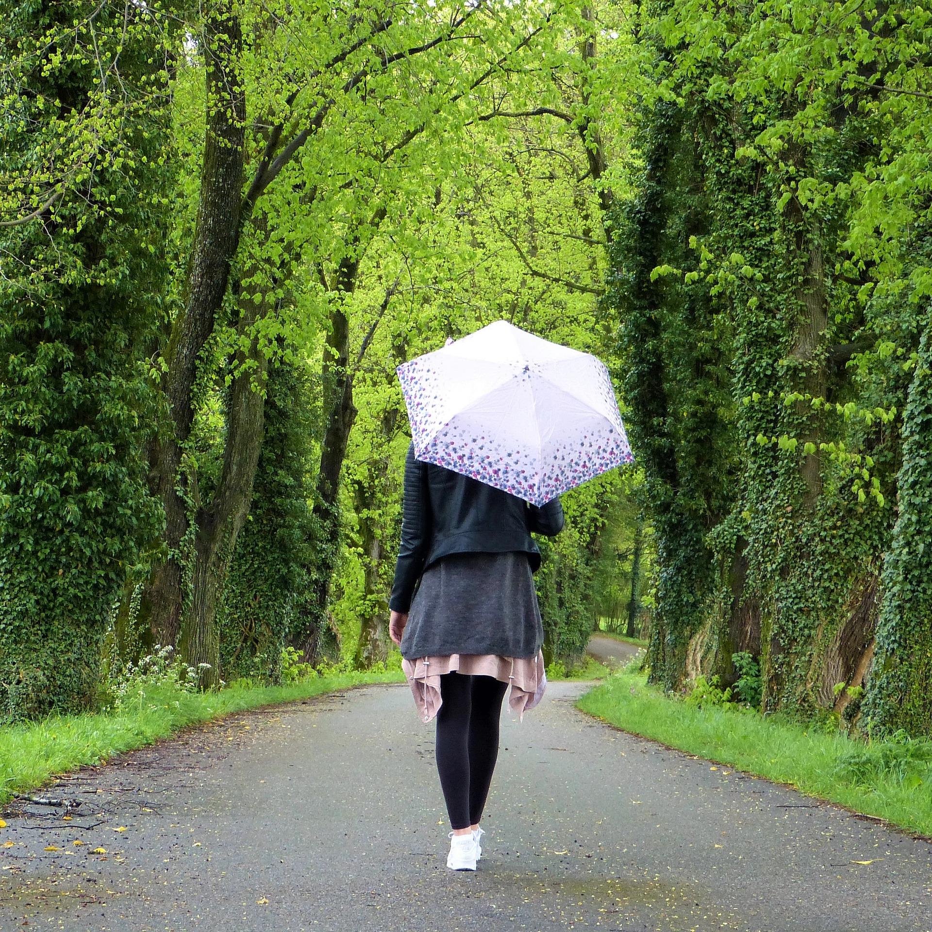 Frau spaziert im Park mit Schirm