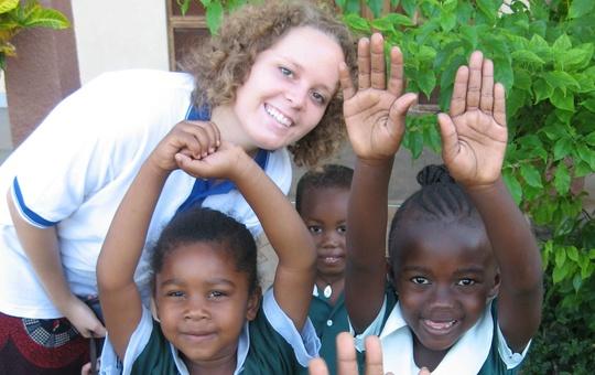 Ein Mädchen lacht mit einer Gruppe afrikanischer Kinder in die Kamera.