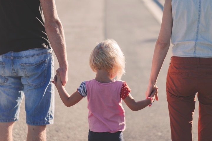 Jugens Mädchen mit Eltern Hand in Hand