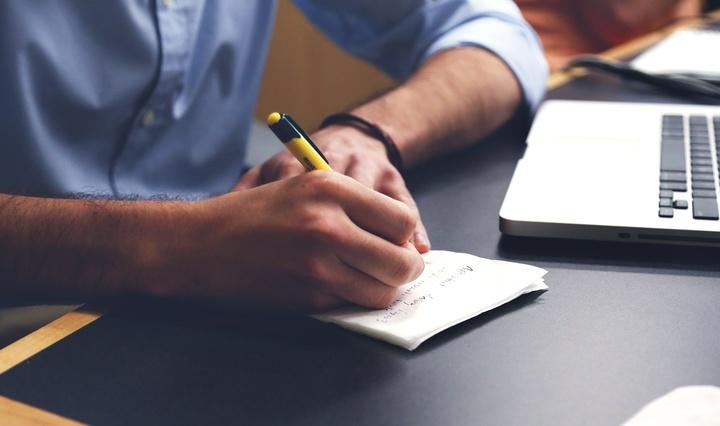 Mann schreibt Notiz am Arbeitsplatz