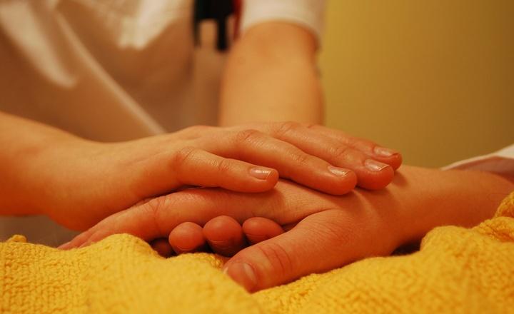 Eine Pflegerin greift die Hand eines Kranken.