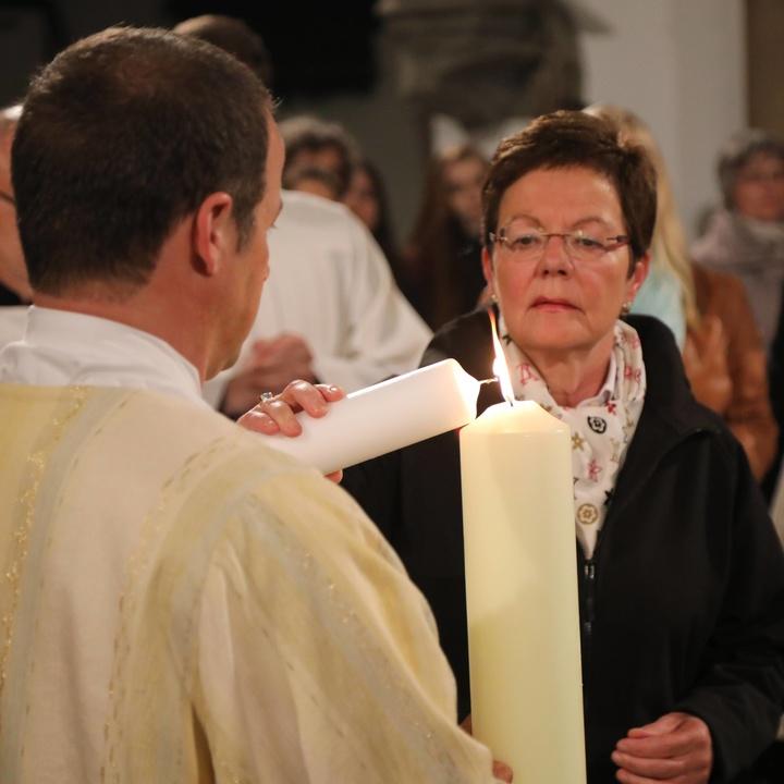 Eine Taufpatin entzündet die Taufkerze.
