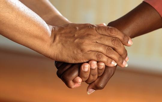 Hände legen sich helfend ineinander.