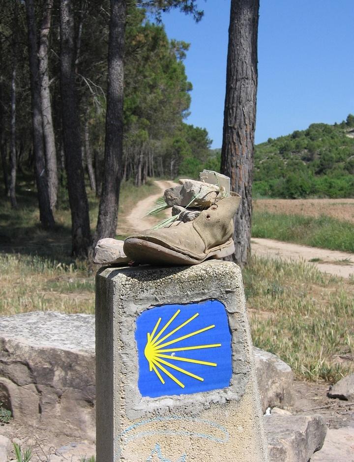 Wanderschuh auf Stein mit gelber Muschel auf blauem Grund für den Jakobsweg