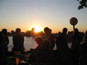 Menschen am Fluss beim Sonnenuntergang.