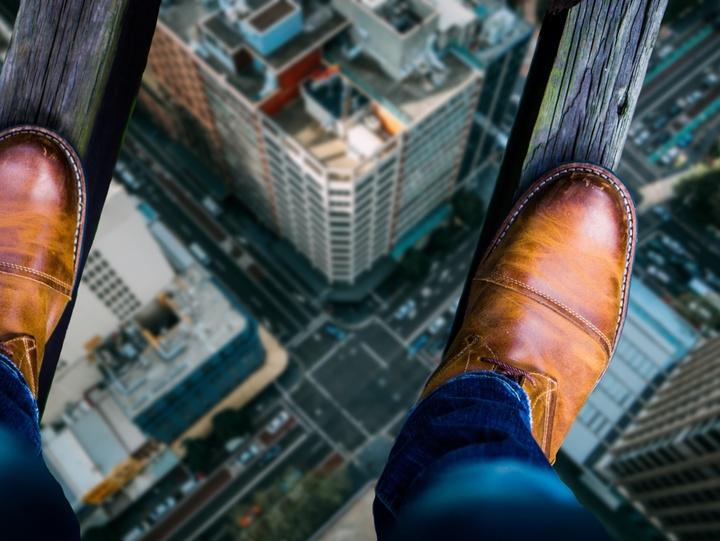Ein Mann balanciert hoch über einer Straße.