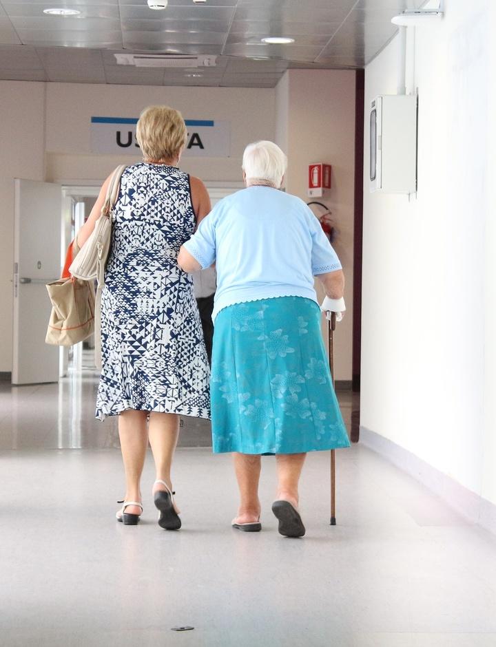 Zwei Frauen gehen über einen Krankenhausflur.