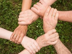 Hände greifen einander: Symbolbild Zusammenhalt