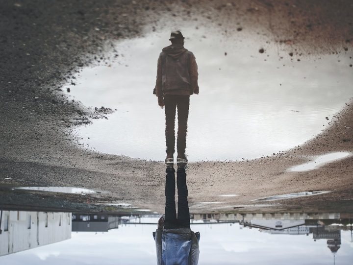 Mann spiegelt sich in Pfütze
