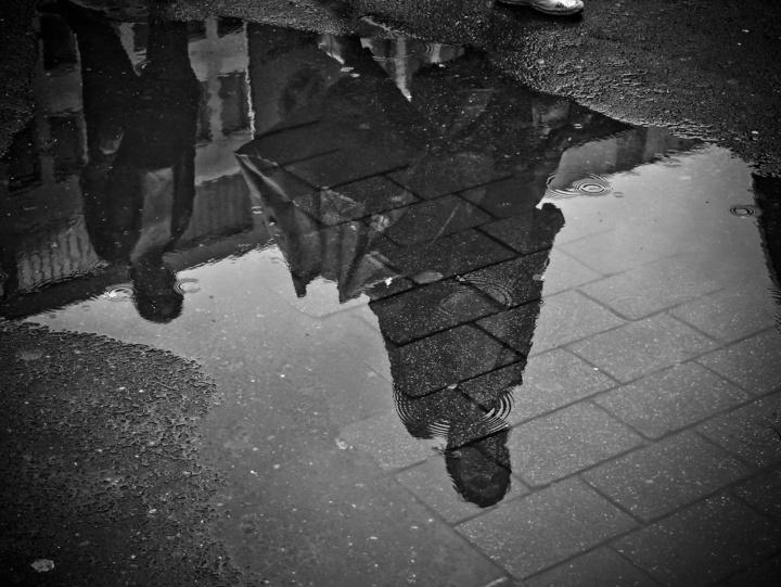 Spiegelbild zweier junger Frauen in einer Pfütze
