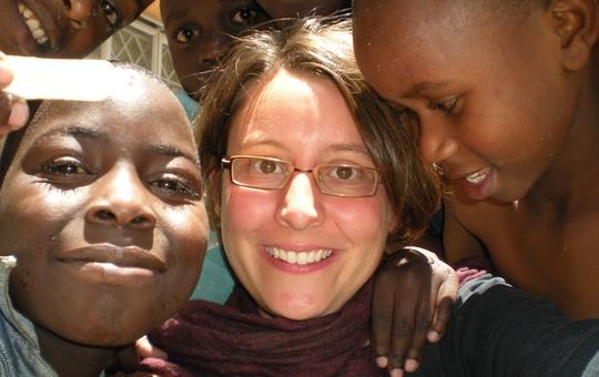 Eine Frau lächelt mit zwei afrikanischen Kindern in die Kamera