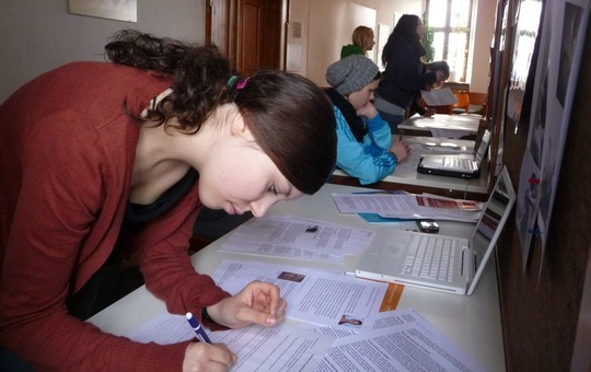Eine junge Frau beugt sich über ein Blatt Papier und schreibt.
