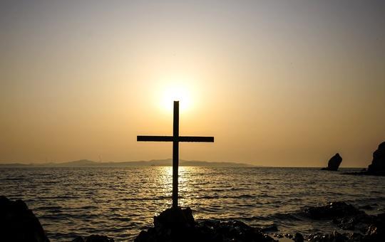 Die Sonne geht am Horizonz unter. Vor dem Meer steht ein Kreuz auf Felsen.