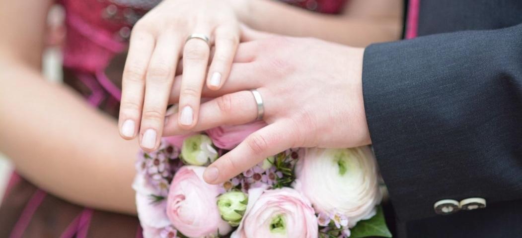 Eine Braut und ein Bräutigam zeigen ihre Eheringe.