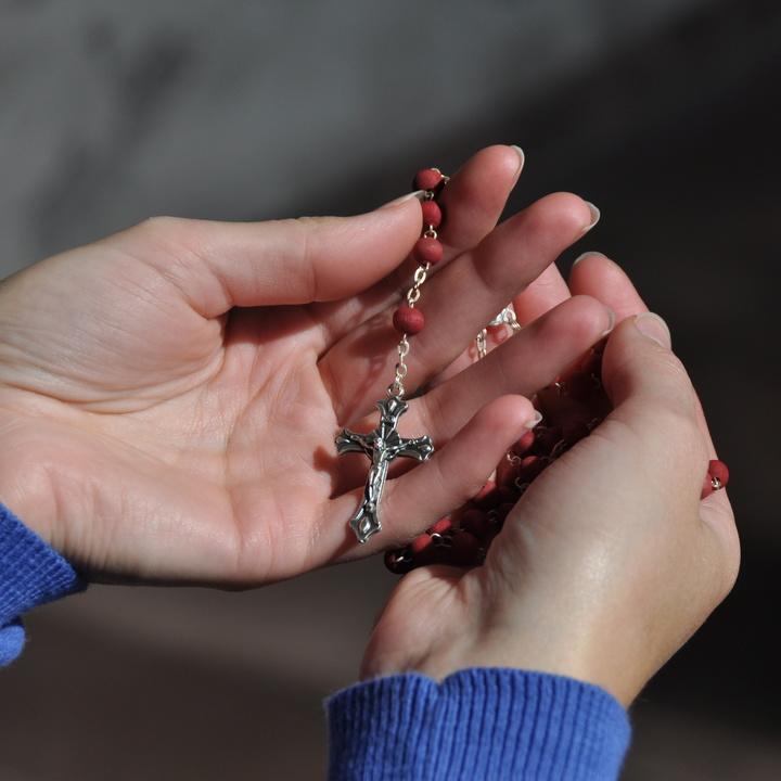 Eine Frau hält einen Rosenkranz in ihren Händen.