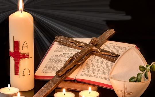 Symbolbild Ostern: Kerze, Kreuz, Bibel und Weihwasser