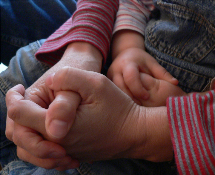 Ein Erwachsener und ein Kind beten gemeinsam. Man sieht die gefalteten Hände.