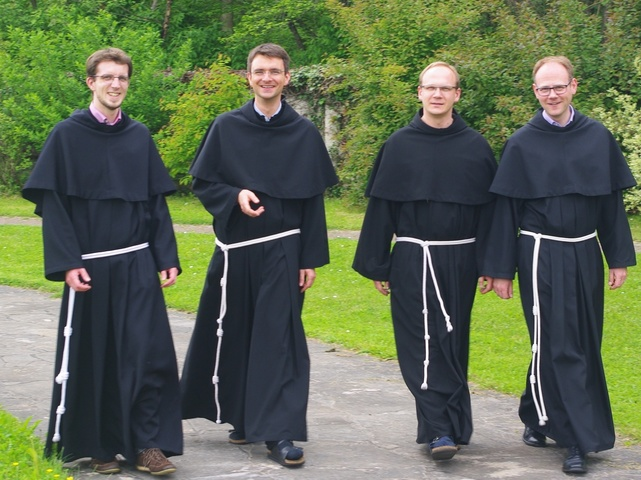 Brüder der Franziskaner-Minoriten laufen einen Weg entlang