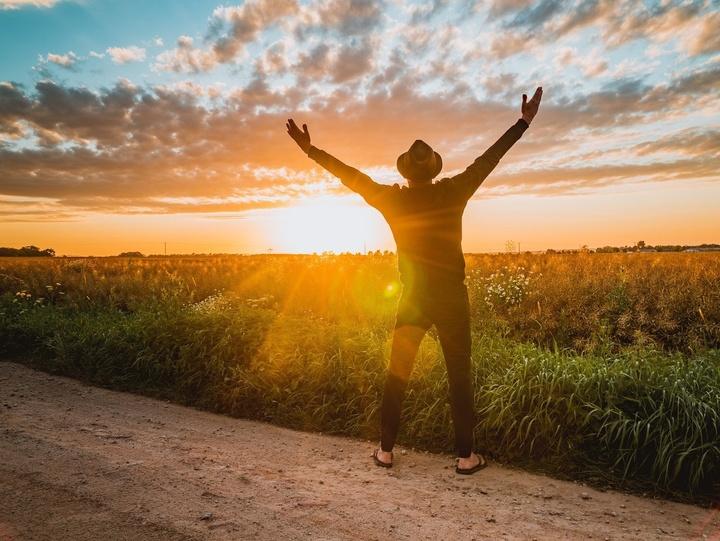 Mann begrüßt den Sonnenaufgang