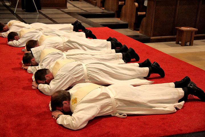 Priesteramtskandidaten liegen vor ihrer Weihe auf dem Boden.