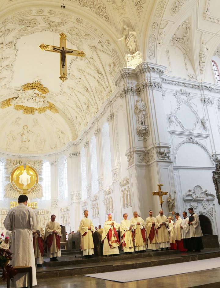 Bischof Friedhelm Hofmann steht gemeinsam mit Konzelebranten im Hochchor des Kiliansdoms.