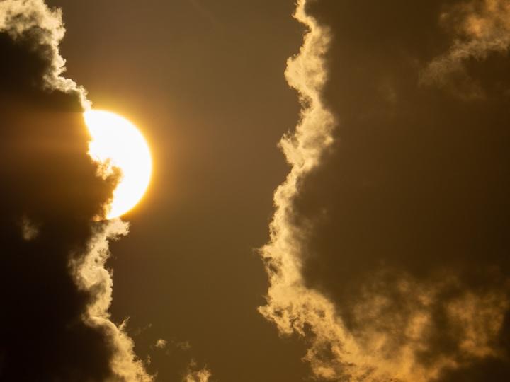 Sonne, versteckt hinter dunklen Wolken
