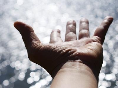 Ausgestreckte Hand über einer glitzernden Wasseroberfläche