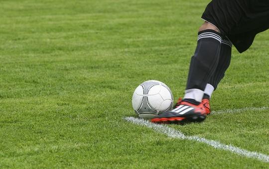 Fußballspieler mit Ball auf dem Platz