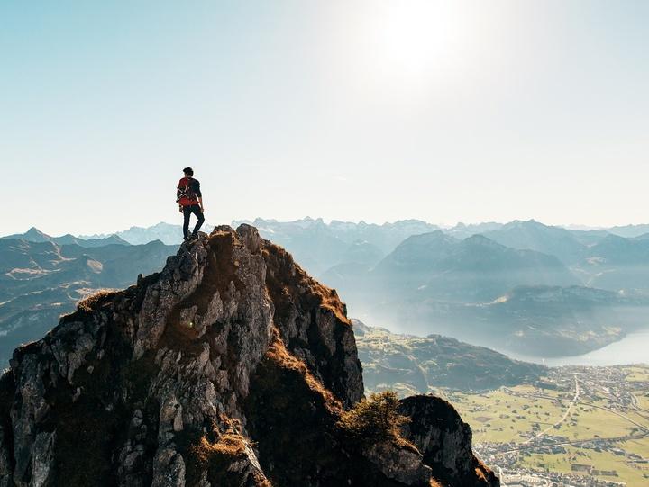 Wanderer blickt auf einem Gipfel in die Ferne
