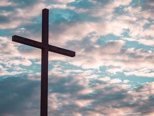Kreuz vor Himmel mit Wolken