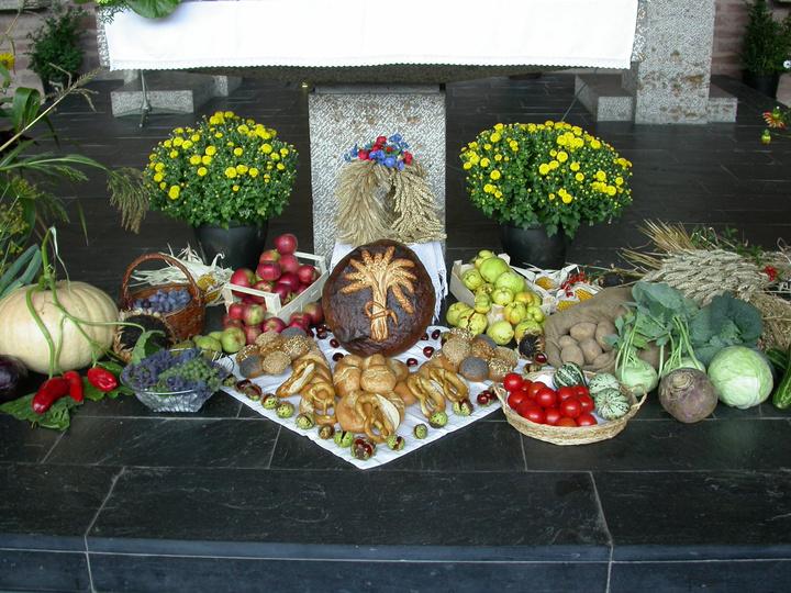 Zu Erntedank liegen vor einem Altar Gaben wie Obst, Gemüse, Blumen und Brot.