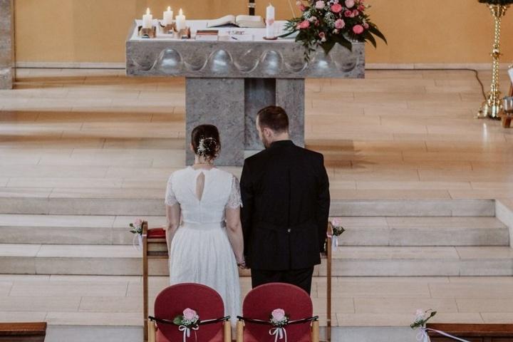 Ein Brautpaar steht in einer Kirche vor den Stufen des Altars.