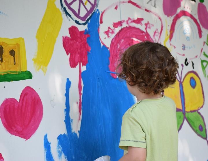 Kind malt mit Pinsel und Farbe an eine Wand.