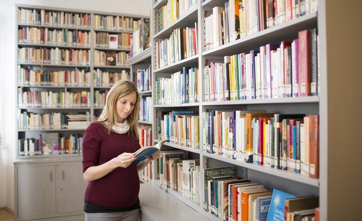 Eine Frau liest in einer Bibliothek ein Buch