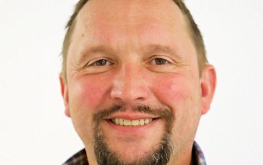 Porträtaufnahme des neuen Afrikareferenten der Diözese Burkhard Pechtl. Er trägt ein bunt kariertes Hemd.