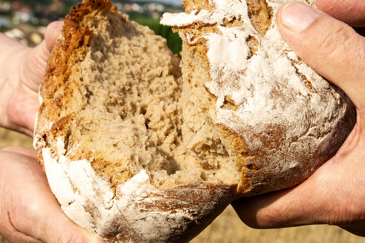 Ein Brot wird geteilt.