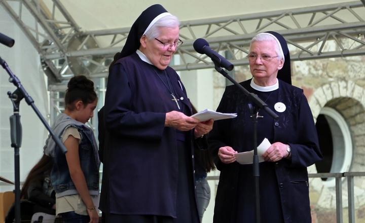 """Zwei Erlöserschwestern stehen beim Fest """"150 Jahre Erlöserschwestern"""" auf einer Bühne."""