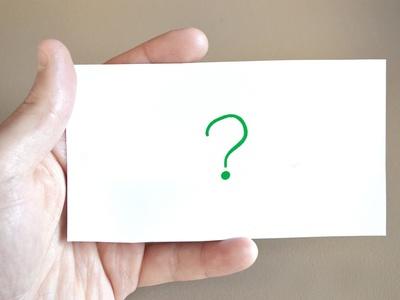 Eine Hand hält eine Karte mit einem Fragezeichen darauf