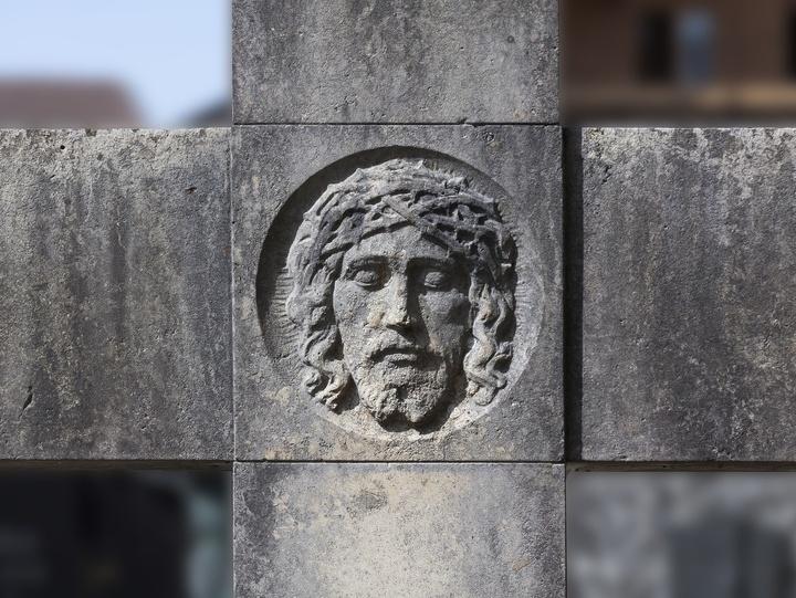 dornengekrönter Jesus auf einem Steinkreuz