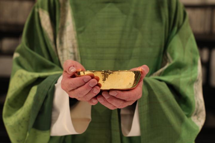 Ein Priester hält eine Patene in der Hand.