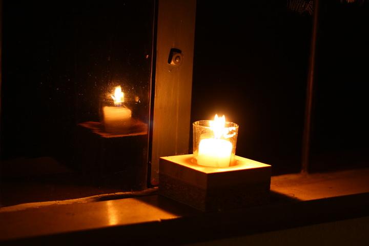 Kerze spiegelt sich im Fenster