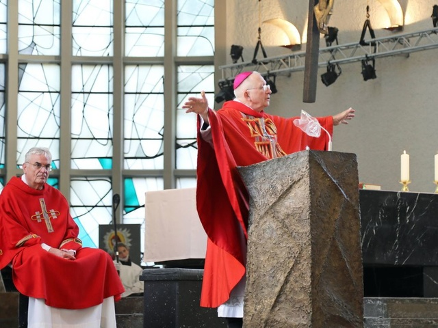 Weihbischof Ulrich Boom steht mit weit ausgebreiteten Armen am Ambo der Schweinfurter Kirche St. Kilian.