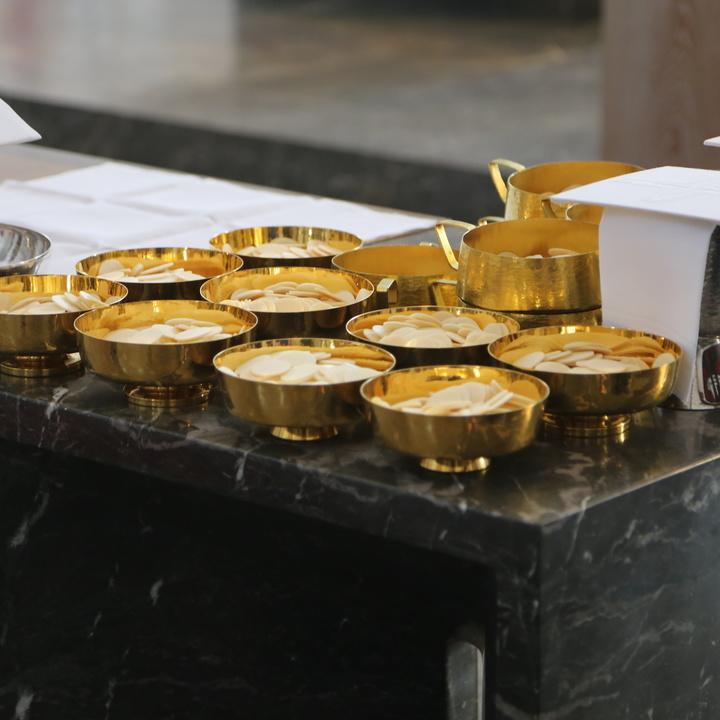 Auf einem Tisch stehen Kelche und Schalen für die Eucharistiefeier.