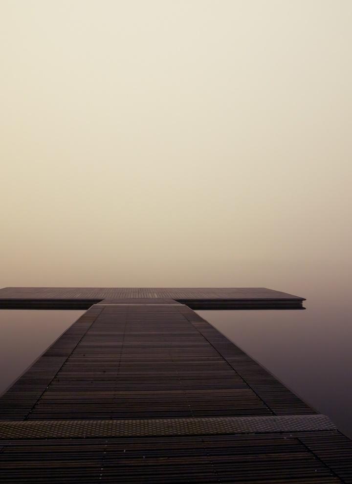 Ein Steg in Kreuzform im Nebel.