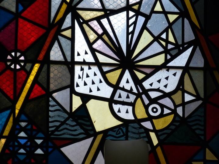 Auf einem Glasfenster ist eine Taube dargestellt.