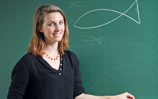 Eine Lehrerin steht vor einer Schultafel auf der ein Fisch gemalt ist