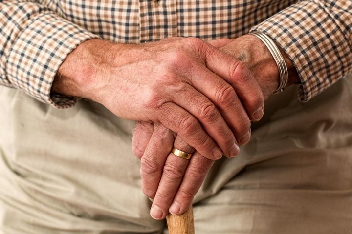 Hände eines alten Mannes mit Gehstock