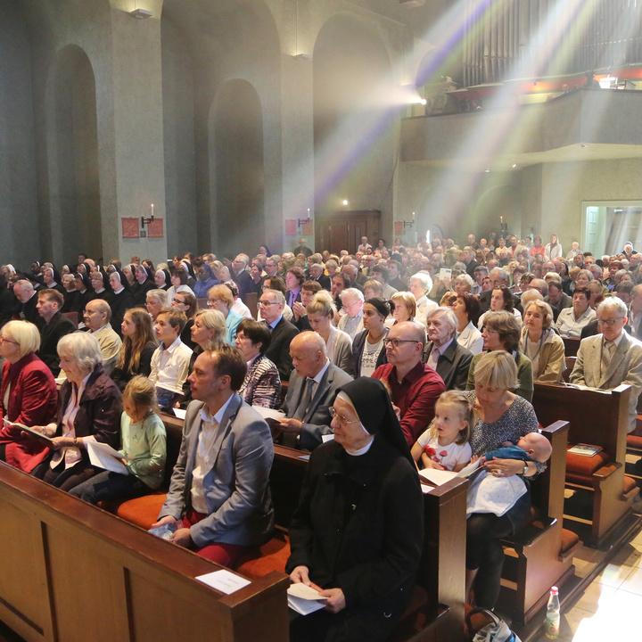 Licht scheint durch ein Kirchenfenster auf Gläubige im Gottesdienst.