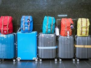 Bunte Rucksäcke auf Koffern